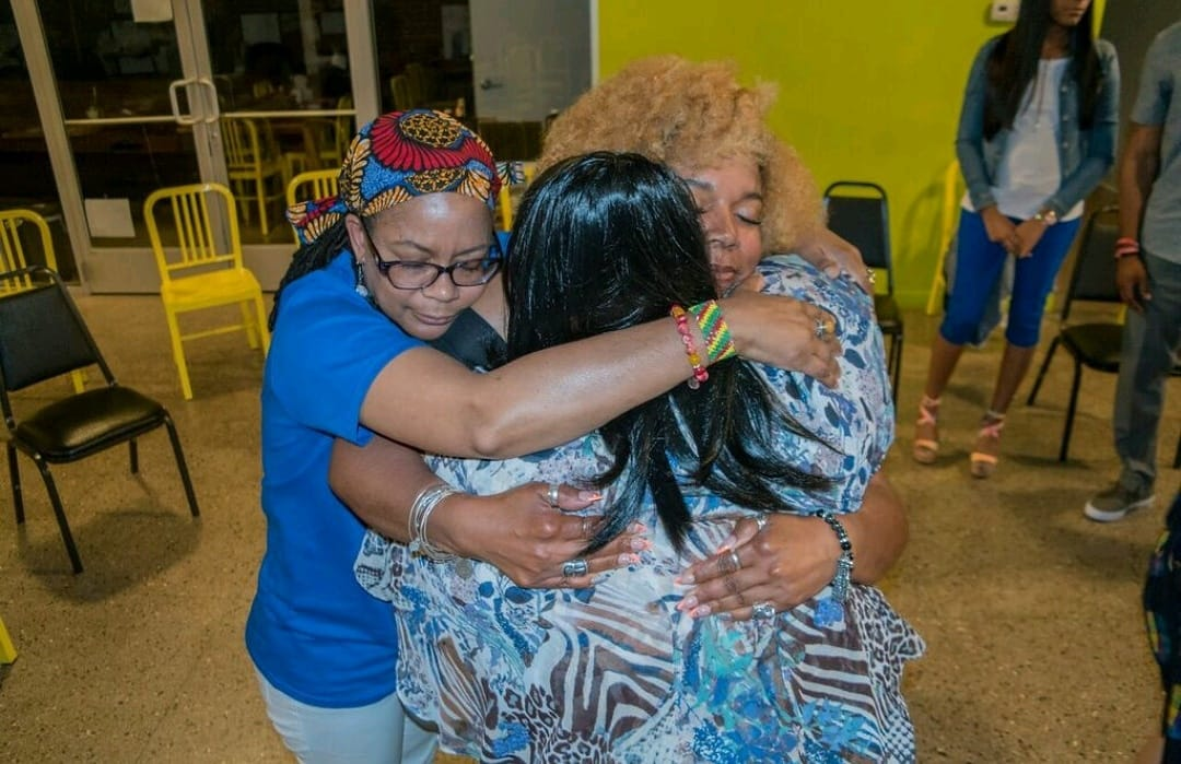 Community members hugging during mental health experience