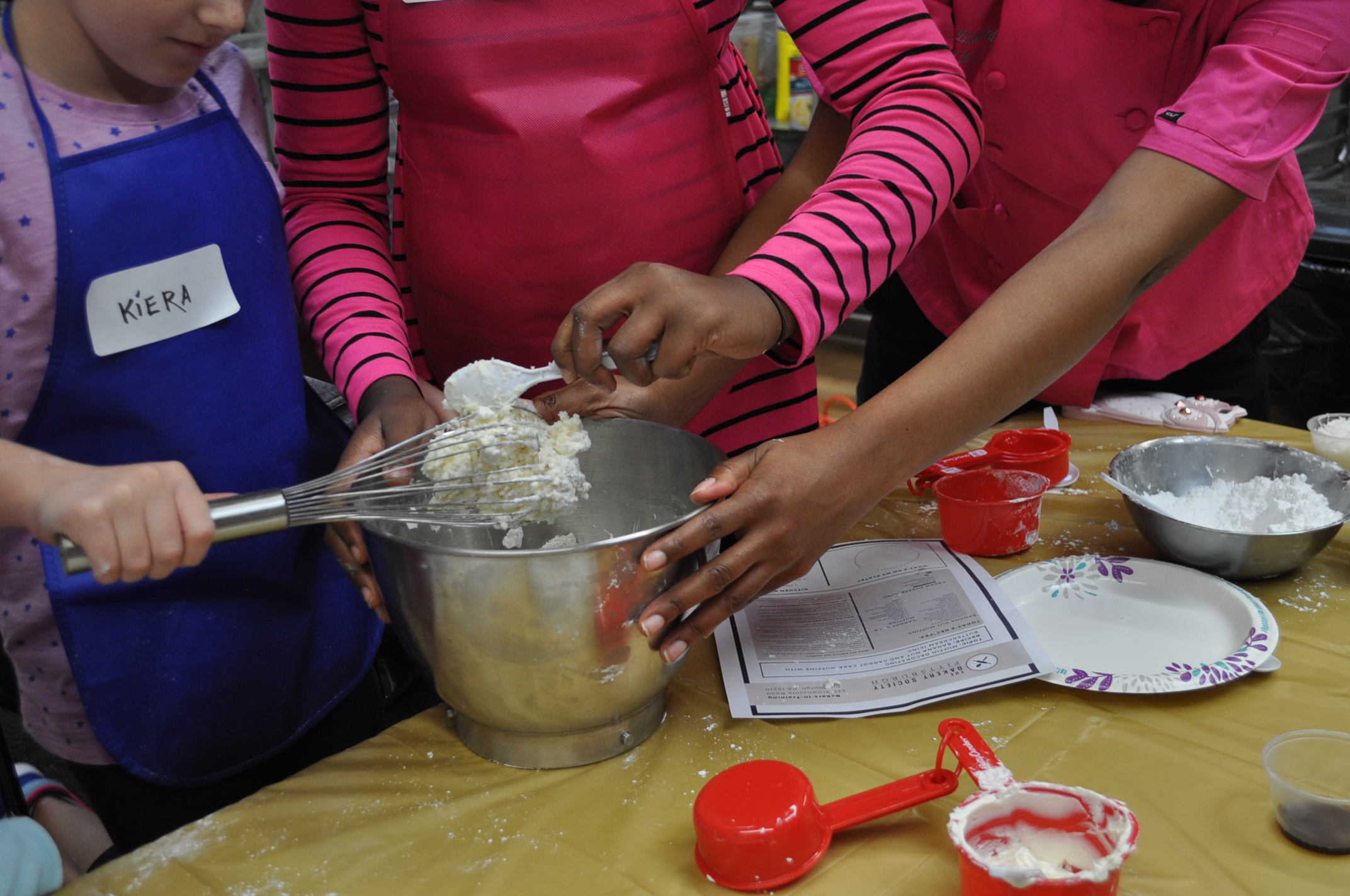 Two children scoop icing off of a whisk into a metal bowl, the instructor leans over the help