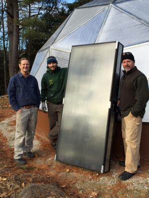 Our project team with a refurbished solar heating panel, ready for installation