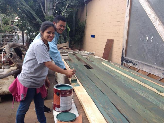 Local student helping to stain wood that will be used to construct the park